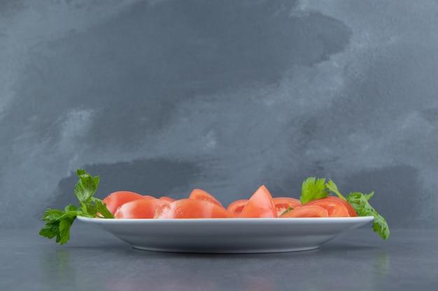 Нарезанные свежие помидоры и петрушка на белой тарелке.