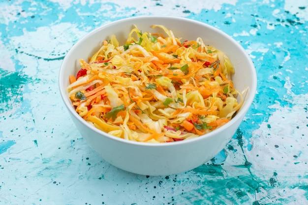 Нарезанные свежие овощи длинные и тонкие кусочки салата внутри круглой тарелки на синем