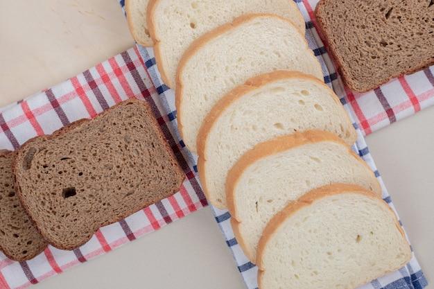 식탁보에 신선한 흰색과 갈색 빵을 슬라이스