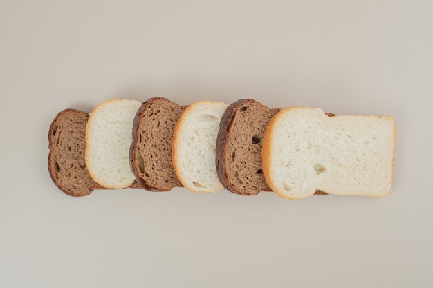 흰색 표면에 신선한 흰색과 갈색 빵을 슬라이스