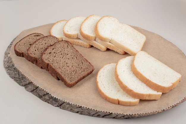木の板に新鮮な白と茶色のパンをスライスしました。高品質の写真