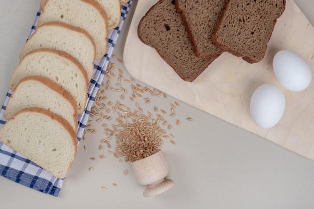 卵とオーツ麦の穀物でスライスした新鮮な白と茶色のパン