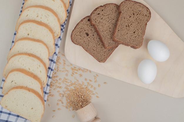식탁보에 계란과 신선한 흰색과 갈색 빵을 슬라이스