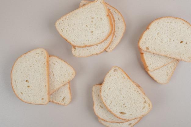Нарезанный свежий белый хлеб на белой поверхности