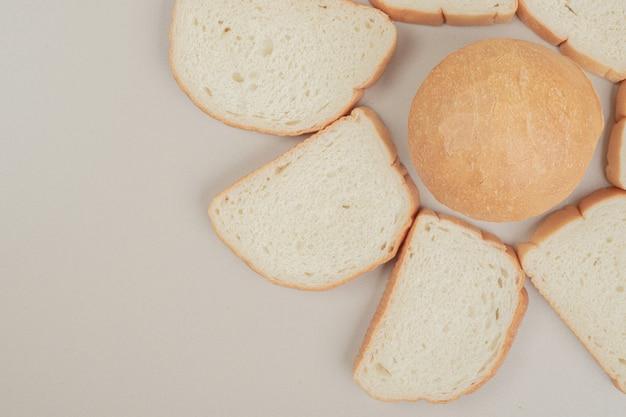Pane bianco fresco affettato sulla superficie bianca