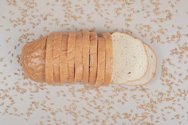 흰색 표면에 귀리 곡물과 신선한 흰 빵을 슬라이스
