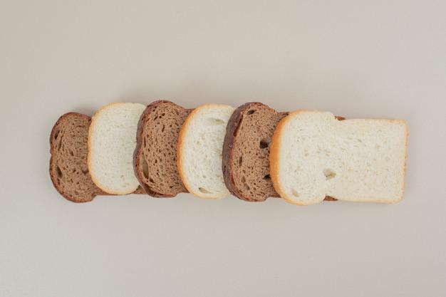 Pane bianco e marrone fresco affettato sulla superficie bianca