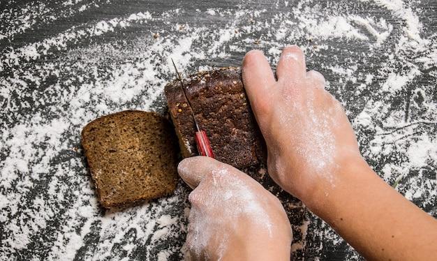 焼きたてのライ麦パンの女性の手をスライスしました。小麦粉と一緒にボード上。上面図