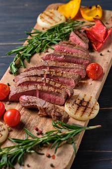 Нарезанный свежеприготовленный стейк с кровью, подается на ветках свежего розмарина на деревянной доске