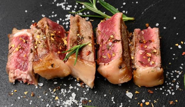 향신료와 함께 검은 색 표면에 튀긴 쇠고기 스테이크 뉴욕 스트립 로스를 얇게 썰어 드문 수준을 닫습니다.