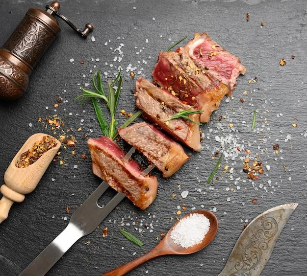 향신료와 함께 검은 색 표면에 튀긴 쇠고기 스테이크 뉴욕 스트립 로스를 슬라이스, 드문 수준, 평면도