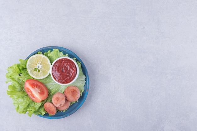 Нарезанные жареные сосиски и кетчуп на синей тарелке. качественная иллюстрация