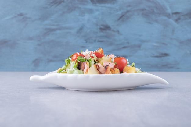 흰색 그릇에 튀긴 된 소시지와 양상추를 썰어.