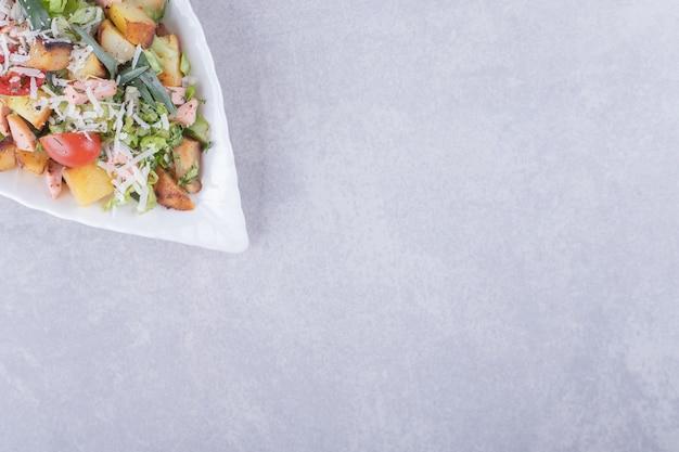 Salsicce e lattuga fritte affettate in ciotola bianca.
