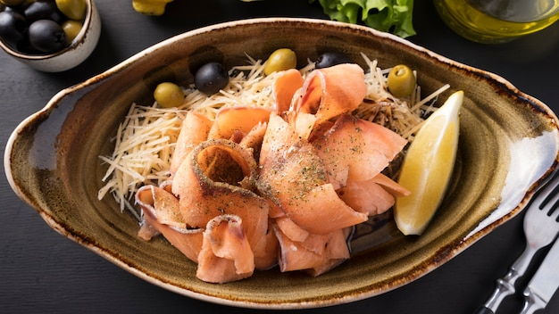 冷凍生サーモンストロガニーナをチーズ、オリーブ、レモンの皿にスライスしました。スライスした冷凍魚。上面図