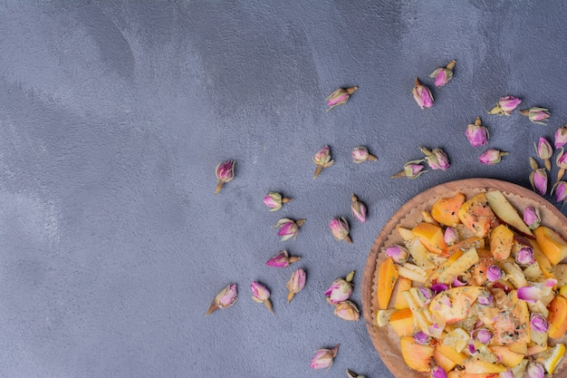 Piatto di frutta a fette con fiori sul blu.