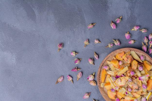 Тарелка нарезанных фруктов с цветами на синем.
