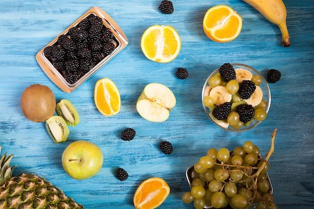 青い木製の背景にスライスされた果物とベリーの上面図。新鮮なトロピカルフルーツの木製テーブル。果物の健康的な自然の新鮮さのミックス