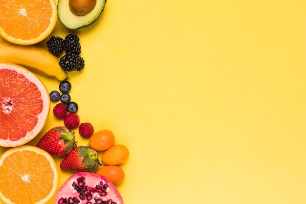 Нарезанные фрукты и ягоды на желтом фоне