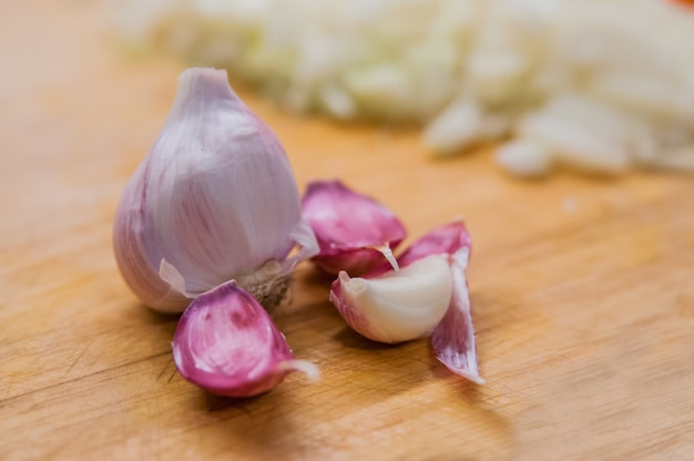 Sliced garlic, garlic clove, garlic bulb in wicker basket place on chopping block on vintage wooden background