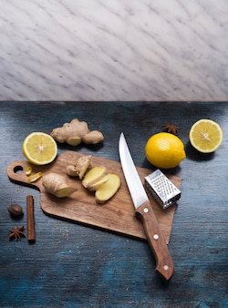 Sliced ginger on wooden board with lemon on table