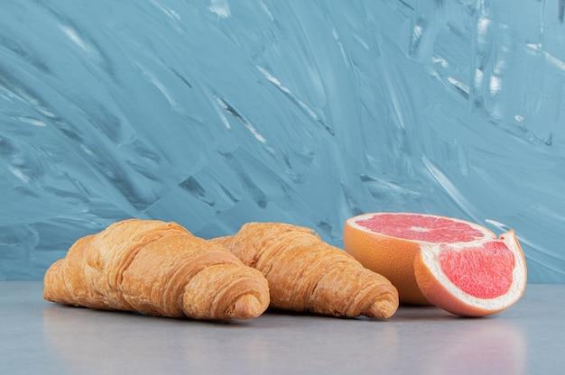 青の背景にスライスしたグレープフルーツとクロワッサン。高品質の写真