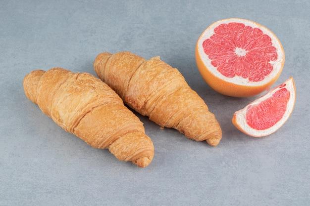 Нарезанный грейпфрут и круассан на мраморном фоне. фото высокого качества