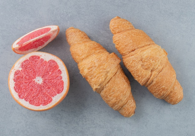 大理石の背景にスライスしたグレープフルーツとクロワッサン。高品質の写真