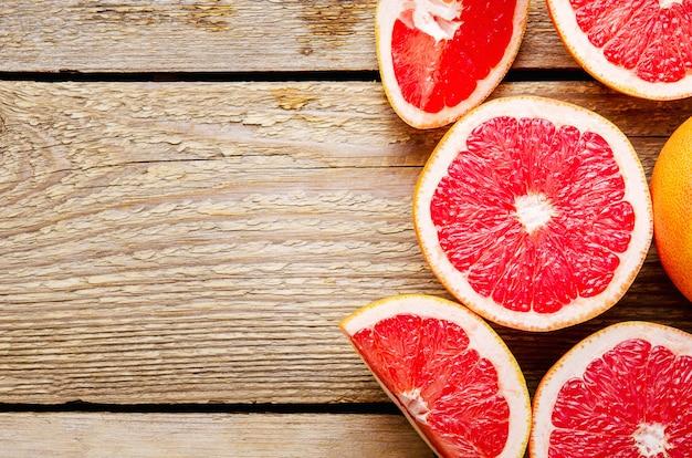 Sliced grapefruit and halves on wooden.
