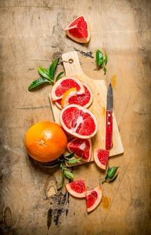 木製のテーブルに葉と木の板にスライスしたグレープフルーツ。上面図