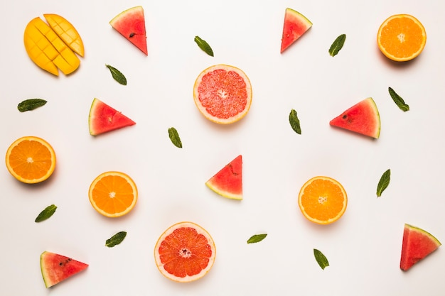 Sliced grapefruit watermelon orange mango and green leaves
