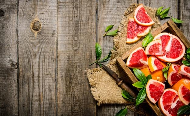 フルボックスと木製のテーブルの葉とスライスしたグレープフルーツ。上面図