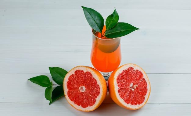 葉と木の表面にジュースとグレープフルーツをスライス、平らに置きます。