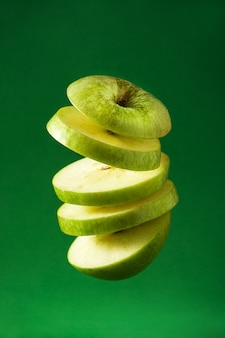 Sliced green apple cut in the air