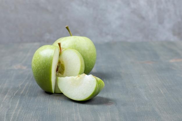 나무 테이블에 고립 된 슬라이스 녹색 사과