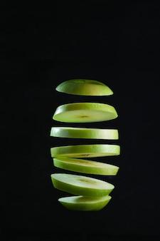 Sliced green apple levitates on black background.