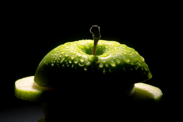 Sliced green apple with water drops over dark background