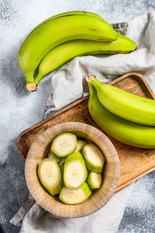 Sliced green banana in a wooden bowl.
