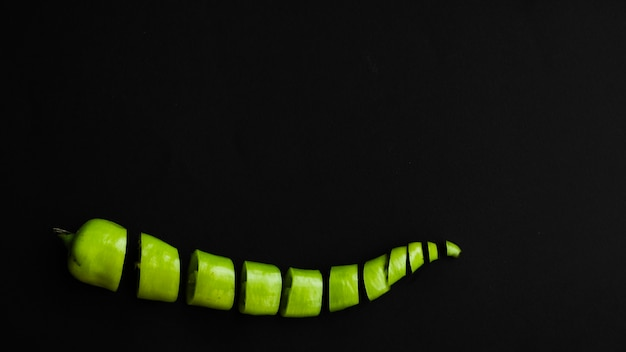 Sliced green chili pepper on black backdrop