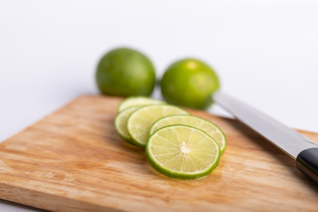 Sliced of the green lime and seed with a knife place on wooden board