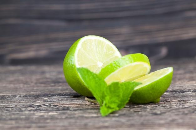 Нарезанный зеленый лайм с листиком мяты во время приготовления