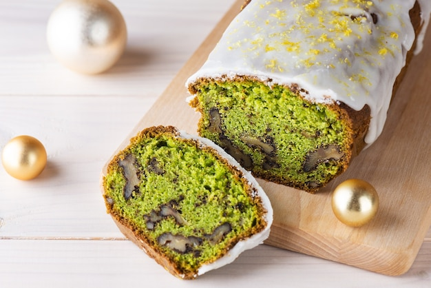 Sliced green muffin with spinach walnut and lemon with christmas balls on a light wooden board