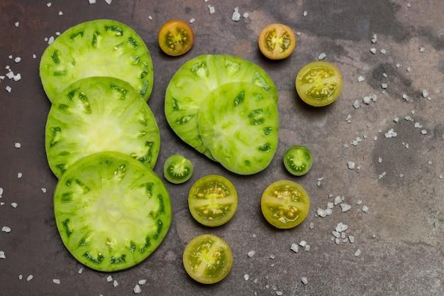 スライスしたグリーントマト。さびた金属の背景。フラットレイ
