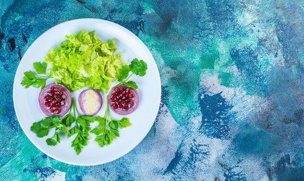 スライスした緑の野菜とザクロの仮種皮を皿に盛り付けます