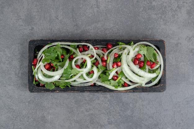 검은 접시에 얇게 썬 채소, 양파, 석류 씨. 고품질 사진