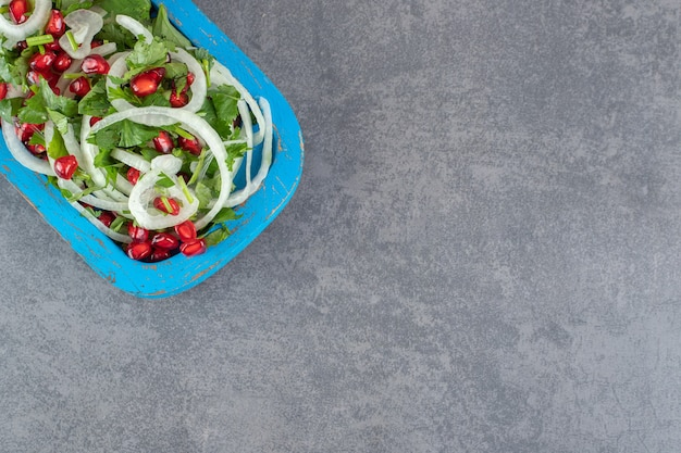 파란색 접시에 얇게 썬 채소, 양파, 석류 씨앗. 고품질 사진