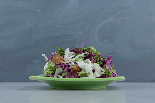 Sliced greens, and red cabbage on a plate , on the marble background.