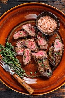 Нарезанные на гриле ломтики стейков грудинки барбекю на деревенской тарелке на деревянном столе. вид сверху.