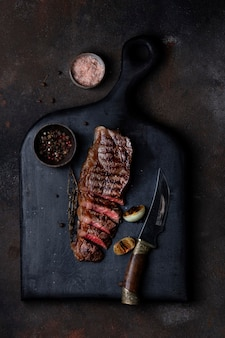 Sliced grilled beef barbecue striploin steak with thyme on a wooden board