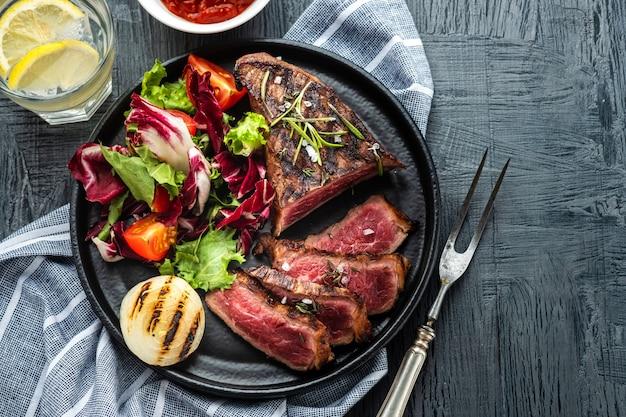 新鮮なサラダと揚げ玉ねぎのグリルした牛肉バーベキュー